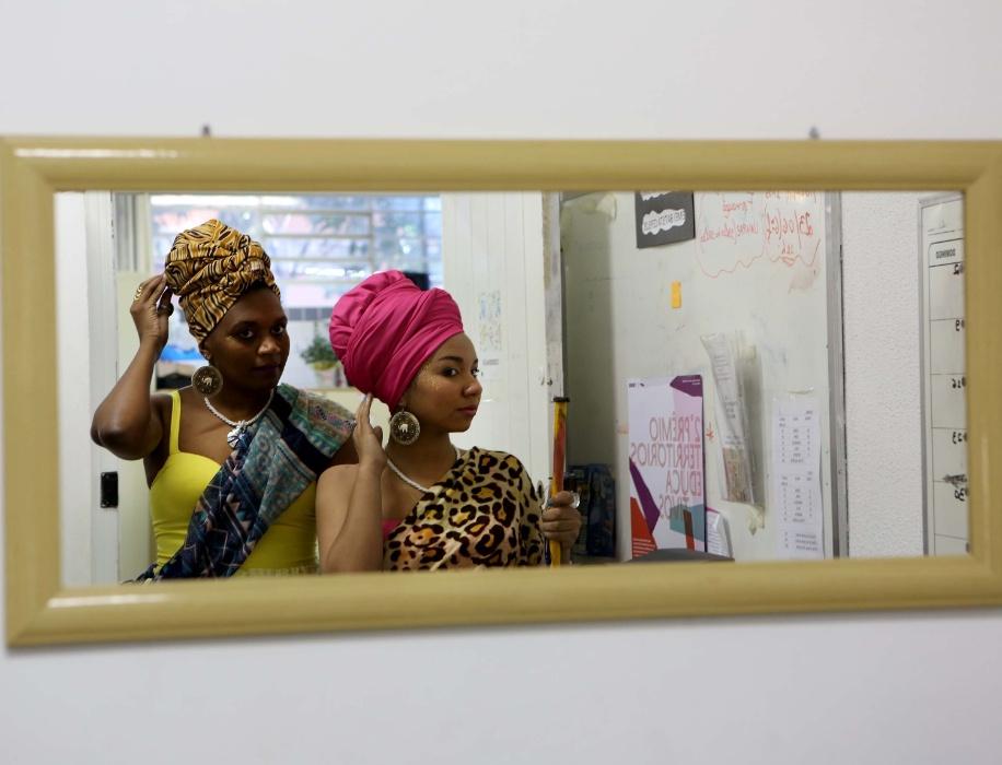 Raísa e Denise usam roupas coloridas, turbante, colares, e brincos típicos africanos para encarnar duas princesas que viajam no tempo para encontrar crianças de escolas e contar um pouco da história delas