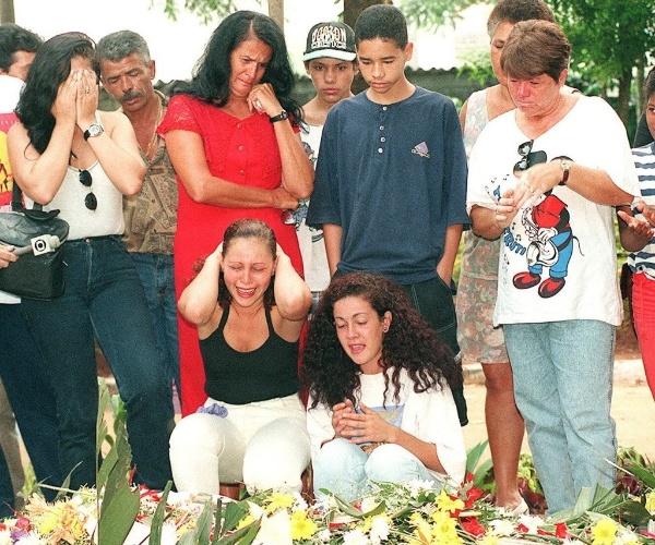 5.fev.1996 - Admiradoras choram diante do túmulo dos integrantes do grupo Mamonas Assassinas, um dia após o enterro, em cemitério de Guarulhos (SP). Bento, Dinho, Júlio e os irmãos Samuel e Sérgio foram enterrados juntos