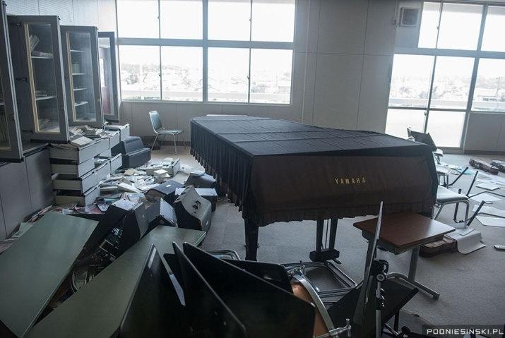 Na imagem, um piano permanece intacto enquanto diversos instrumentos musicais se encontram espalhados pelo chão de uma escola