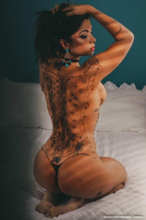 Coberta com uma tatuagem de henna, Dani Sperle exibe suas curvas em ensaio