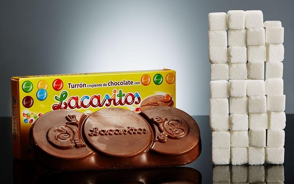 """Você já comeu chocolates que vêm cobertos com uma casquinha colorida? O chocolate Lacasitos, popular na Espanha, é um tablete """"recheado"""" com aqueles confeitos coloridinhos. 200 g desse chocolate contem 140 g de açúcar, o equivalente a incríveis 35 torrões de açúcar"""