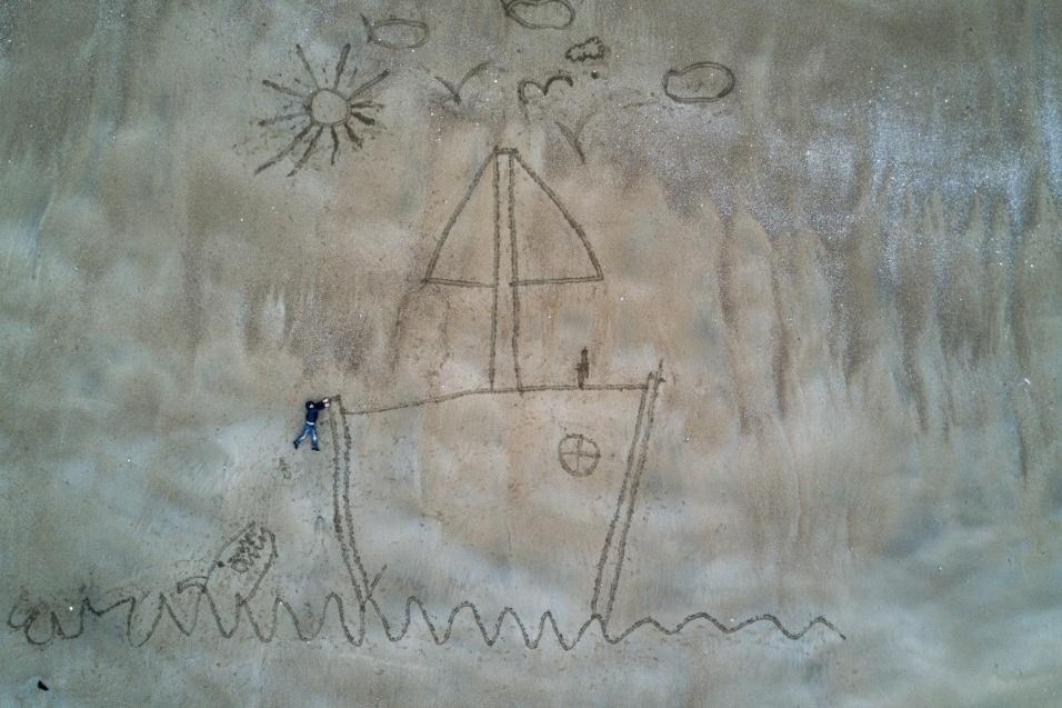 """Uma imagem com um desenho de um barco na areia e um garoto supostamente pendurado levou o segundo lugar na categoria """"criatividade"""""""
