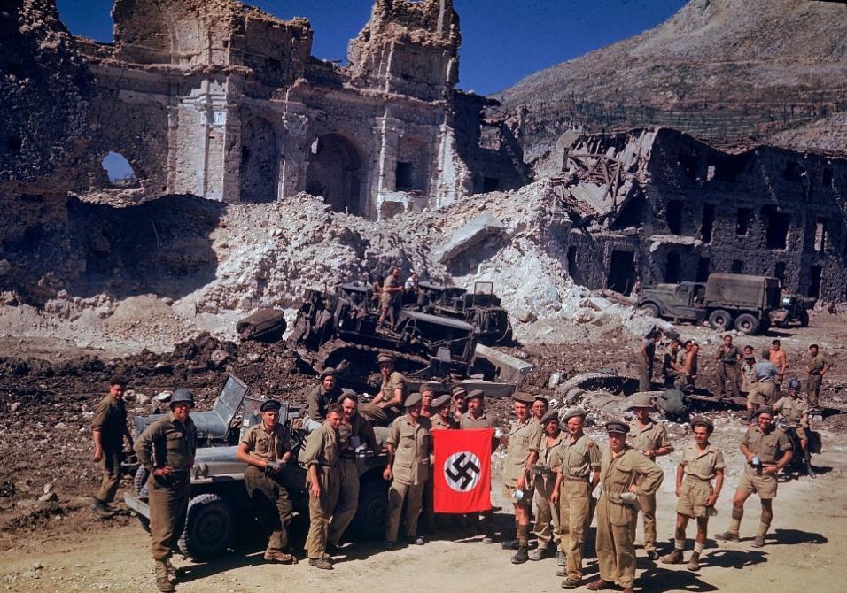 1943 - Soldados britânicos e sul-africanos exibem bandeira nazista como prêmio após limparem escombros da cidade de Cassino