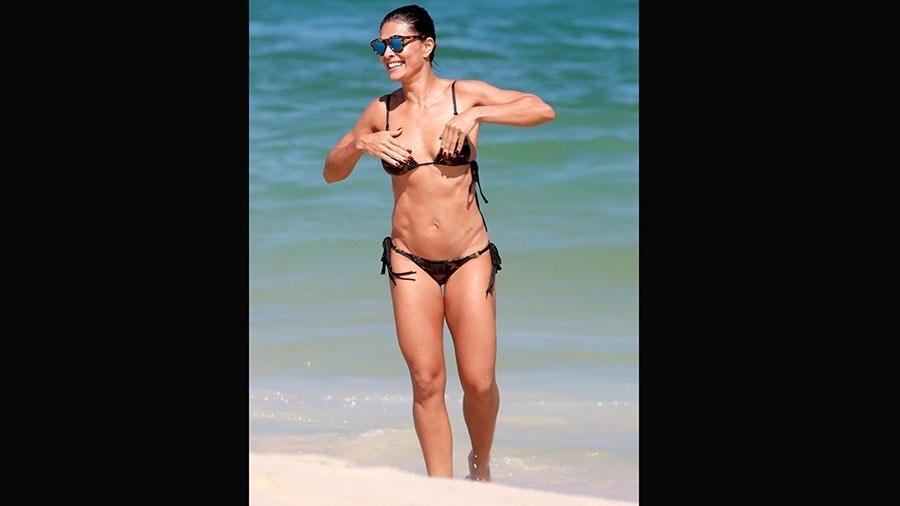 3.abr.2016 - Juliana Paes dá ajeitadinha no biquíni após tomar banho de mar