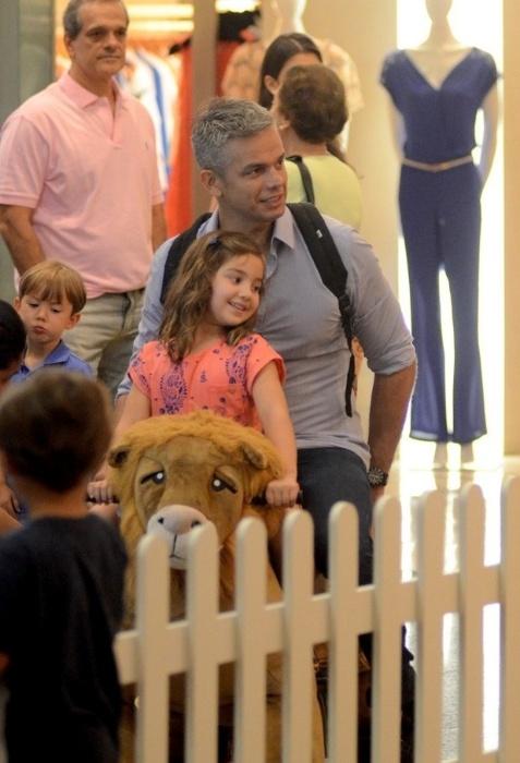 16.nov.2015 - Depois de Flávia Alessandra, Otaviano Costa não resiste ao carrinho em formato de leão e brinca com a filha, Olívia, em um shopping do Rio