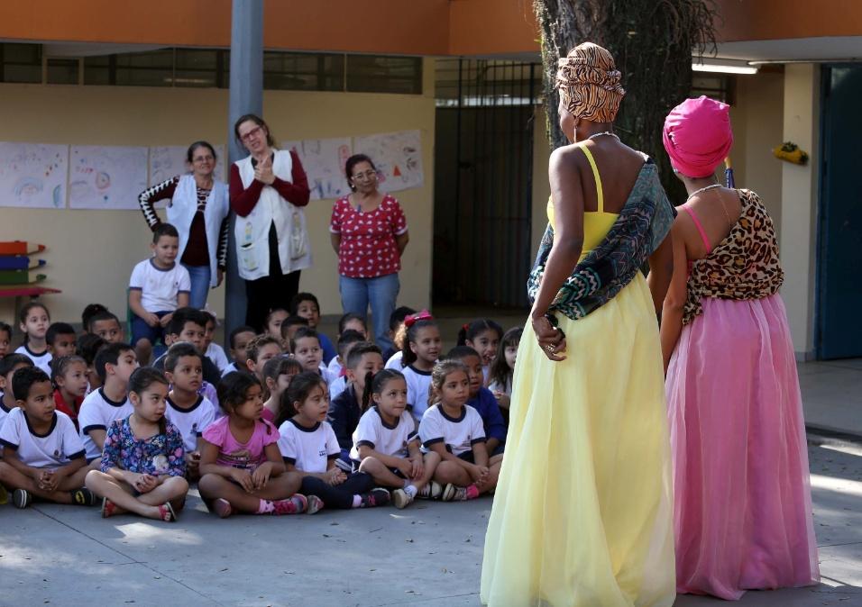 Crianças, atentas, recebem as universitárias Denise (dir.) e Raísa (esq.). Elas encarnam as princesas Kambo e Funji para mostrar um pouco da cultura afro-brasileira em uma performance na EMEI Batista Cepelos
