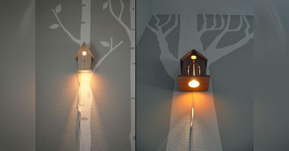 26. Luminária feits com uma casinha de passarinhos presa a uma árvore pintada na parede