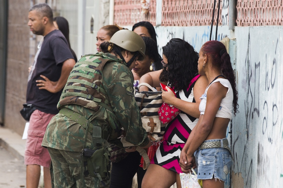 20.fev.2018 - Polícia revista população na favela Kelson, região Norte do Rio de Janeiro durante intervenção federal