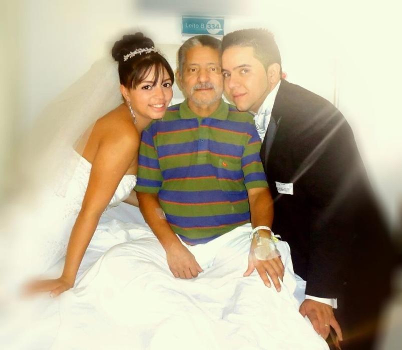 """Ana Carolina de Jesus Moreira Sanches e Felipe Sanches da Silva, de São Paulo (SP), em 14 de julho de 2013. """"Meu pai, José Simplicio da Silva, na data do nosso casamento encontrava-se internado no hospital, mas como fazíamos questão de ter a foto com ele fomos até o hospital público no horário de visita e entramos vestidos de noivos e registramos este momento, foi muito emocionante."""""""