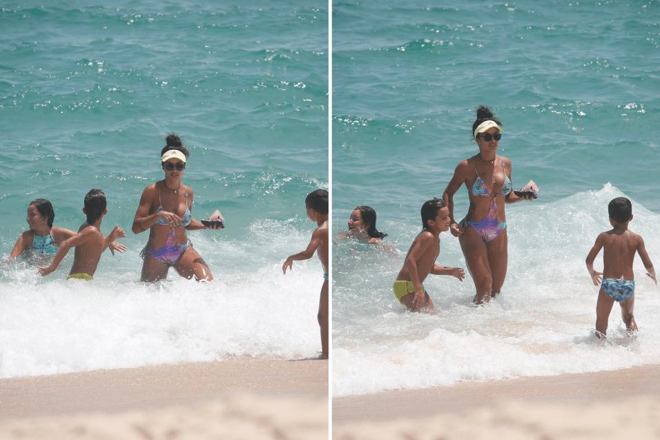 12.jan.2017 - Cercada por crianças, Aline Riscado deixa a água na praia da Macumba