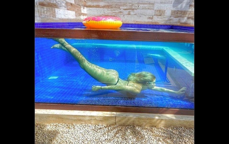 """17.out.2016 - A modelo Bárbara Evans chamou atenção pelas curvas ao mergulhar em piscina com lateral de vidro. Na imagem, é possível ver a gata submersa, trajando um biquíni fio dental preto. """"Maravilhosa! Belas curvas"""", escreveu um fã de Bárbara no Instagram"""