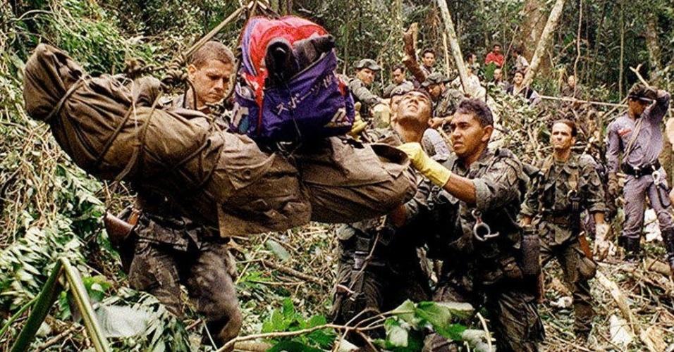 3.mar.1996 - Na noite do dia 2 de março, o Learjet de prefixo PT-LSD, que levava os cinco integrantes do grupo Mamonas Assassinas, mais um segurança e um assistente da banda, decolou às 21h58 de Brasília (DF) com destino a Guarulhos (SP). Quando estava próximo de pousar no Aeroporto Internacional de São Paulo (Cumbica-GRU), o piloto fez uma manobra equivocada após arremeter o avião e, às 23h16, o jatinho chocou-se na Serra da Cantareira. De acordo com a versão do Departamento de Aviação Civil (DAC), o avião vinha em uma velocidade alta a cerca de 10 quilômetros do aeroporto, e necessitou desistir de pousar. Só que no processo de arremetida, o piloto efetuou uma curva para a esquerda, quando deveria fazer para a direita. Na foto, bombeiros resgatam corpo de vítima do acidente aéreo