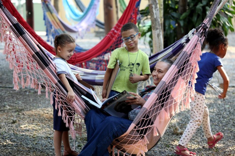 Professora Cibele. Cibele lê um livro enquanto crianças observam a diretora da EMEI Nelson Mandela
