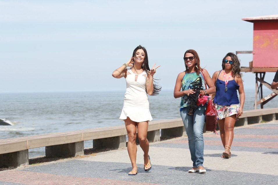18.ago.2015 - A bailarina Aline Riscado posou, nesta terça-feira, para um ensaio fotográfico na praia da Barra da Tijuca, no Rio de Janeiro. Um dos looks da morena era um vestido branco curtinho; entre uma pose e outra, ela acenou para o paparazzo e mostrou carisma