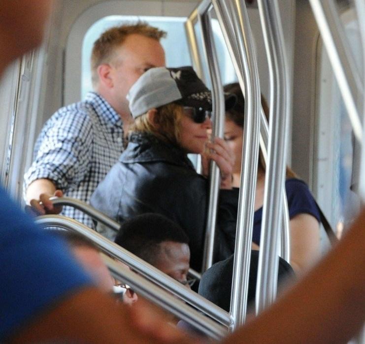 29.jul.2015 - Musa pop também não tem o menor problema em usar o metrô. Na imagem, Madonna aparece irreconhecível de boné e óculos de sol