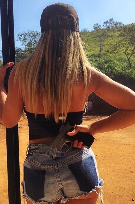 """27.jul.2015 - Sem perder a sensualidade, Renata Frisson - mais conhecida como Mulher Melão - compareceu à aula de tiro na Associação de Tiro Duque de Caxias (RJ) vestida de shortinho curto, blusa decotada e botas de cano e salto altos. Isso porque a funkeira fará o papel de bandida no clipe """"5 horas"""". """"Fiz o curso de tiro para aprender a segurar a arma, atirar, recarregar, tudo de verdade. Quero o máximo de realismo no clipe. Se é para ser bandida, que seja a melhor"""", contou a beldade"""