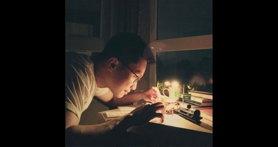 O artista Derrick Lin montando uma de suas miniaturas