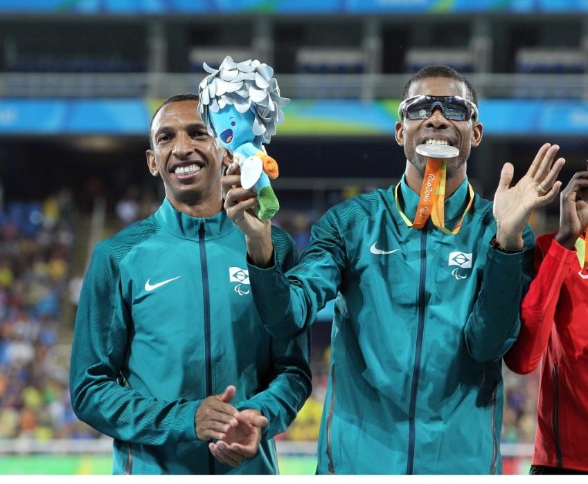 13.set.2016 - Odair Santos (dir.) morde a medalha de prata conquistada na prova dos 1.500 m, na categoria T11