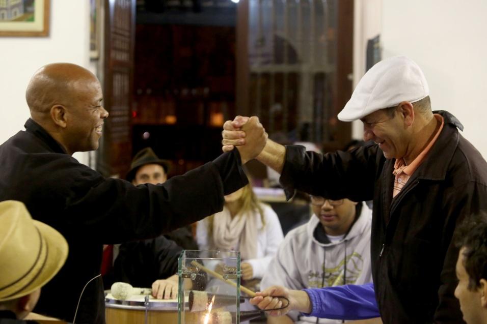 Embalados pela batucada do Smaba da Bela, Caio Prado e Chapinha se cumprimentam em momento de amizade e união musical