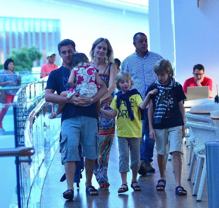 20.mar.2016 - Eva ganha colo de Luciano Huck em dia de passeio com a mãe e os irmãos - Benício (de camiseta amarela) e Joaquim - em um shopping no Rio de Janeiro