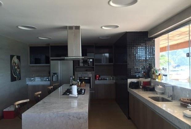 Jan.2017 - Cozinha completa da propriedade inclui fogão com coifa na bancada central do ambiente