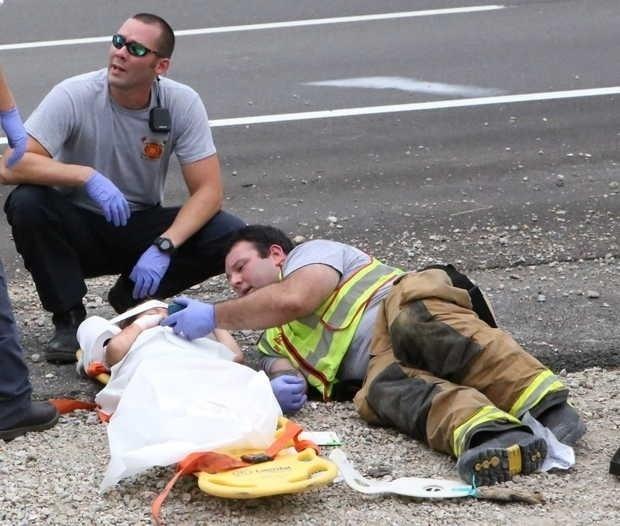 """7.set.2015 - O bombeiro Casey Lessard virou notícia após socorrer uma criança ferida em um acidente de carro na cidade de D'Iberville, no Mississippi (EUA), e colocar um filme infantil em seu celular para acalmá-la. As imagens, publicadas no Imgur, mostram o bombeiro deitado no chão ao lado da criança com o aparelho na mão. Na ocasião, Casey escolheu o filme ?Happy Feet? para entreter a criança. E deu certo! """"O vídeo a tranquilizou instantaneamente"""", declarou Darren Peterson, chefe de Casey e capitão do Corpo de Bombeiros de D'Iberville, ao The Sun Herald"""