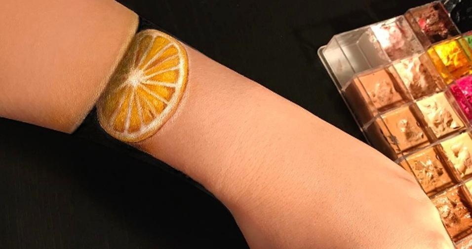 7. Além do rosto, Mimi também cria ilusões com outras partes de seu corpo, como, por exemplo, nesta imagem em que seu braço virou uma fatia de laranja