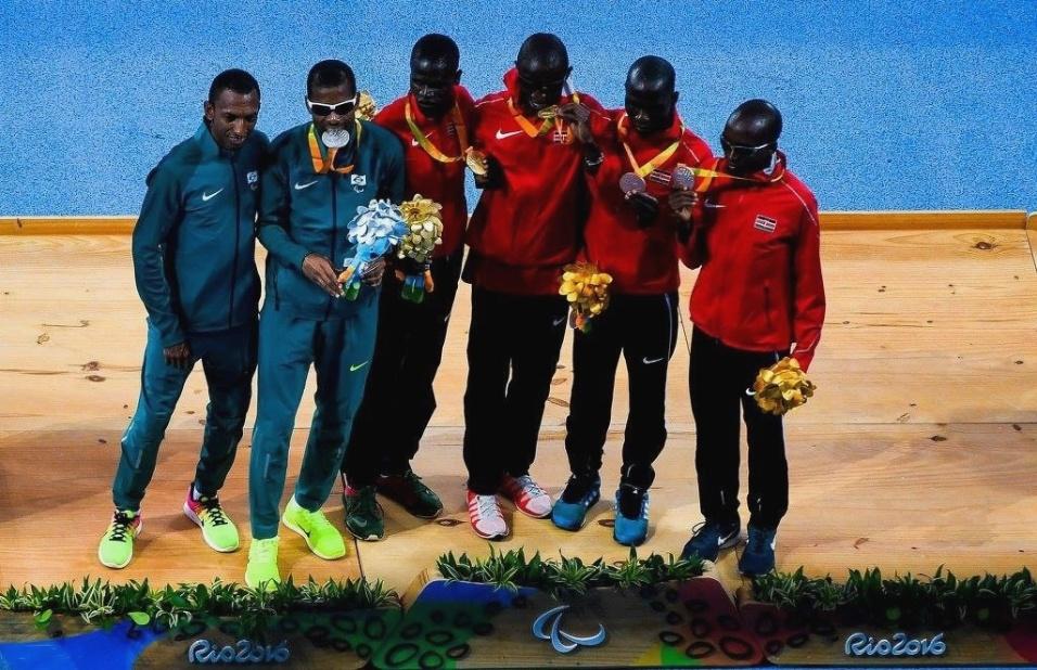 8.set.2016 - Odair Santos (mordendo a medalha) conquistou a prata na prova dos 5.000m - T11