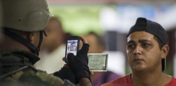 23.fev.2018 - Oficial do Exército tira foto de morador da Vila Kennedy durante operação na favela
