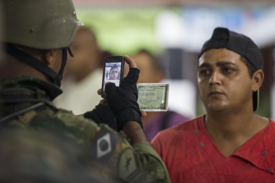 23.fev.2018 - Oficial do Exército tira foto de morador da Vila Kennedy para fichamento durante operação na favela
