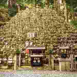 """15.jan.2017 - O cemitério japonês também é constituído de várias estátuas de Jizo, que foi um pequeno monge que morreu quando era criança. Por este motivo, alguns pais que perderam seus filhos pequenos vão ao local e """"vestem"""" essas estátuas, trajando pequenas roupas que simbolizam o luto. Lápies sobrepostas pertencentes às pessoas que não tinham amigos e familiares também dão um tom sinistro ao local - Reprodução/MegaCurioso"""