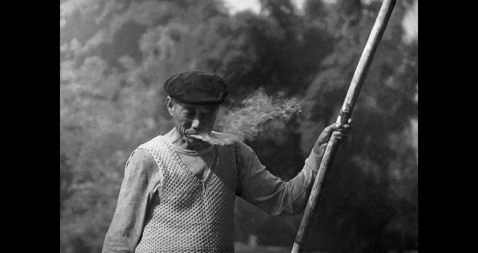 5. A fumaça que se destaca na paisagem atrás do homem que solta fumaça de cigarro