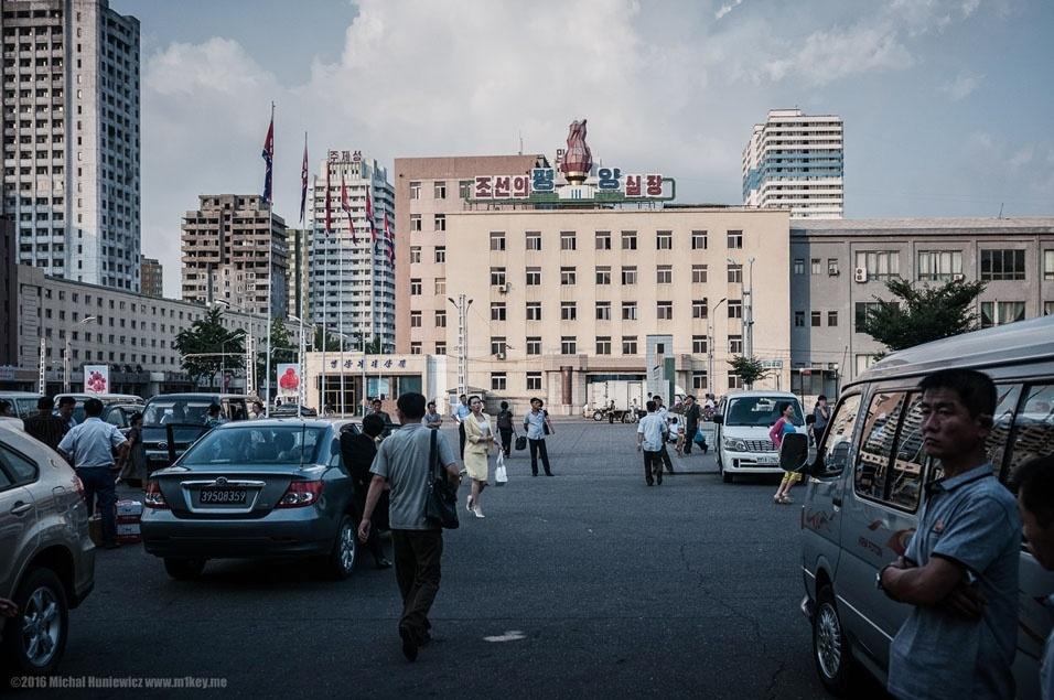 """35. """"A poucos passos da plataforma, fomos interceptados por nossos dois guias, que não nos deixaram até o final da viagem, com algumas exceções no hotel. Ao sair da estação de trem, Pyongyang parece uma cidade comum, embora bastante limpa e não muito barulhenta e cheia"""""""