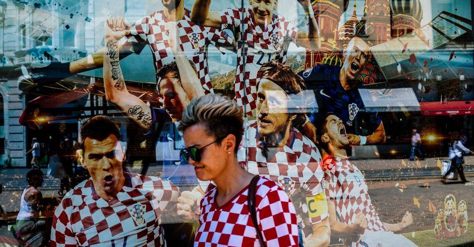 Em Zagreb, torcedora da Croácia passa em frente a mural que ilustra a seleção da Croácia e a Praça Vermelha