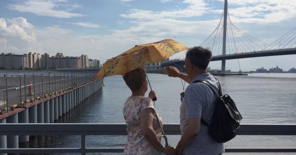 Russos tentam se proteger do sol. Temperatura é de 27°C.
