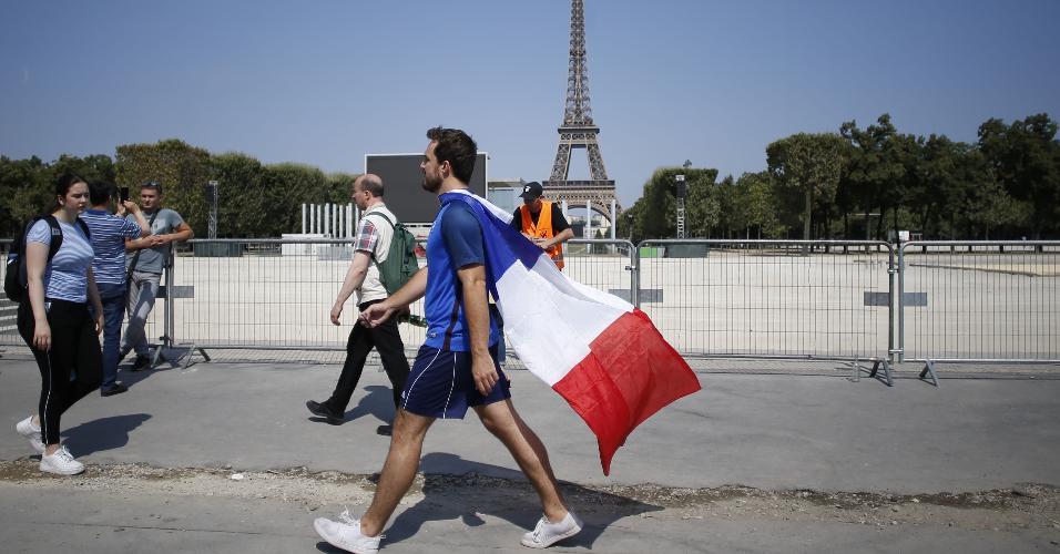 Torcedor vestido com as cores da França caminha pelas ruas de Paris