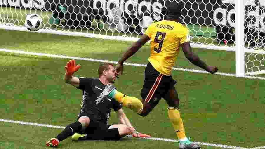 Romelu Lukaku chuta por cima de  Farouk Ben Mustapha para marcar terceiro gol da Bélgica contra Tunísia - Catherine Ivill/Getty Images