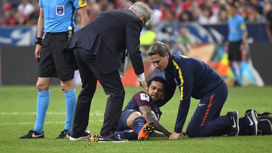 Daniel Alves é atendido pelo departamento médico do PSG durante jogo contra o Les Herbiers - AFP PHOTO / Damien MEYER