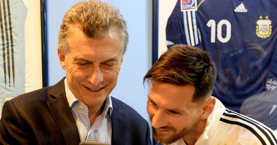Mauricio Macri, presidente da Argentina, mostra um vídeo a Lionel Messi no celular