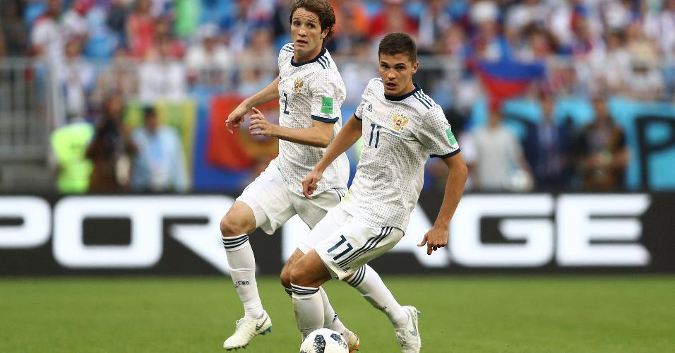 Roman Zobnin, da seleção da Rússia, carrega a bola e é observado por Mario Fernandes em jogo contra o Uruguai