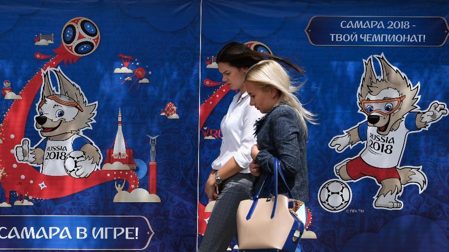Duas russas passam em frente a pôster da Copa do Mundo - Stu Forster/Getty Images