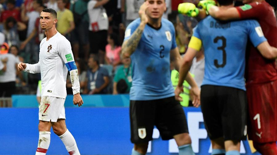 Cristiano deixa o campo observando os carrascos José Giménez (2) e Diego Godín (3) - Jonathan Nackstrand/AFP