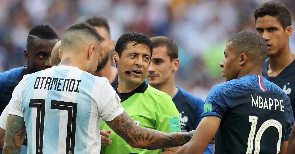 Nicolas Otamendi, da Argentina, reclama com o juiz iraniano Alireza Faghani, cercado por jogadores da França