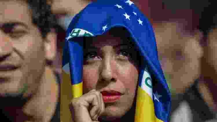 Torcedora se protege do sol com a bandeira do Brasil - AFP PHOTO / Miguel SCHINCARIOL - AFP PHOTO / Miguel SCHINCARIOL