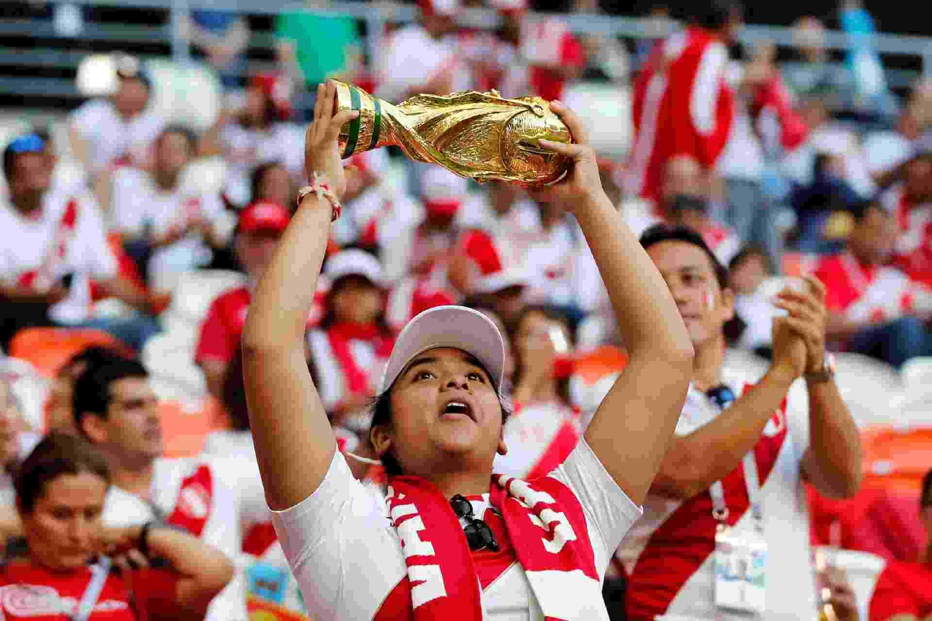 Torcedora do Peru ergue réplica de taça da Copa do Mundo antes de jogo contra a Dinamarca - Carlos Garcia Rawlins/Reuters