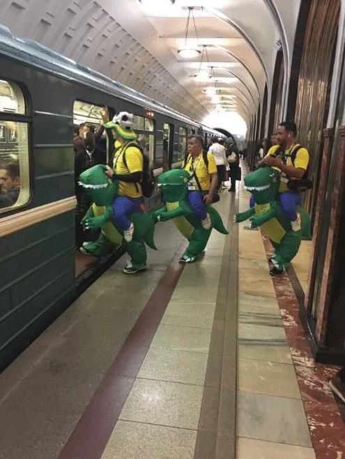 Brasileiros no metrô de Moscou com fantasias de dinossauro