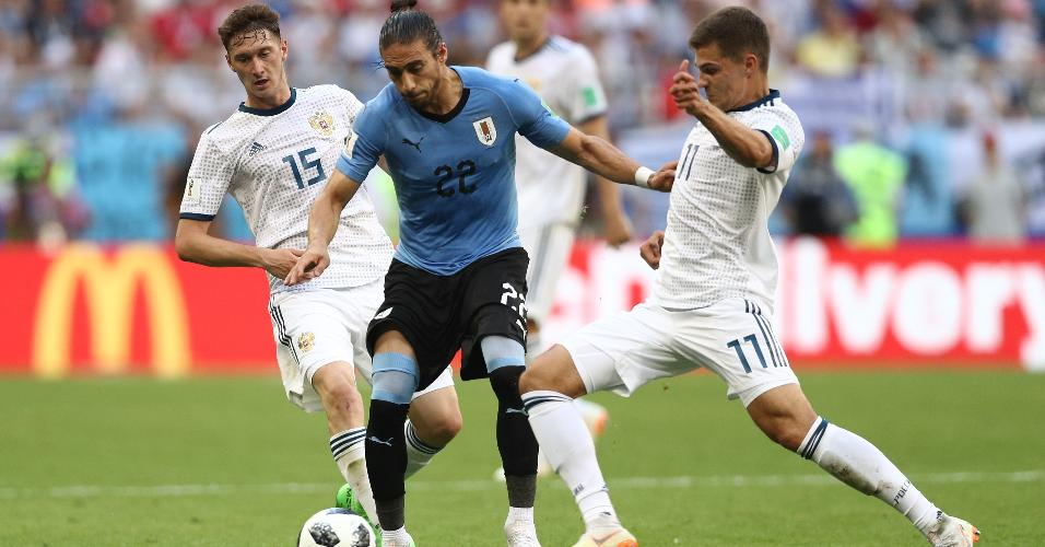 Martin Caceres, da seleção do Uruguai, é marcado por Roman Zobnin e Alexey Miranchuk, da Rússia