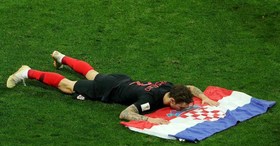 Sami Vrsaljko, da Croácia, comemora a classificação para a final beijando a bandeira da Croácia
