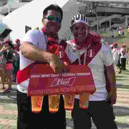 Dupla de torcedores peruanos se diverte com copos de cerveja antes do último jogo da seleção na Copa - UOL