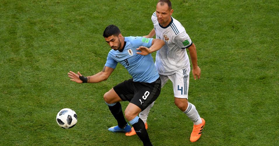 Luis Suarez, da seleção do Uruguai, é marcado por Sergey Ignashevich, da Rússia